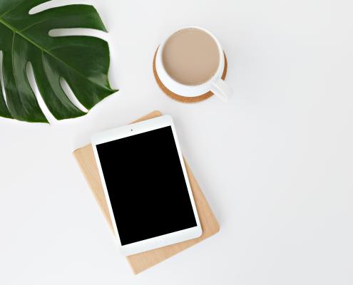 un mini ipad e una tazza di caffè su un tavolo bianco