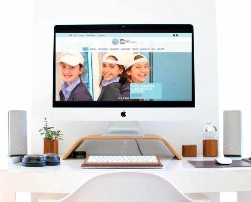 un computer su una scrivania bianca e l'homepage di un sito