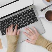 due mani che battono la tastiera di un computer portatile