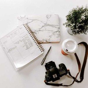 una scrivania con una macchina fotografica, un quaderno con appunti , una tazza di caffe è una piantina