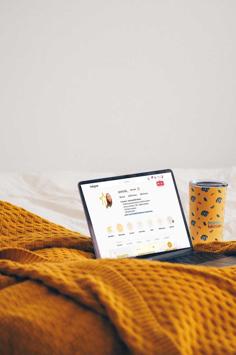 un laptop aperto sopra un letto con una coperta vicino